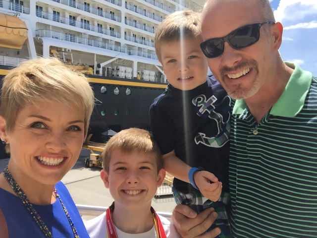 Family photo outside Disney Cruiseline Terminal in front of Disney Fantasy